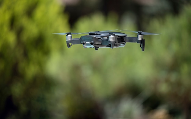 Dark grey drone flying over a green background