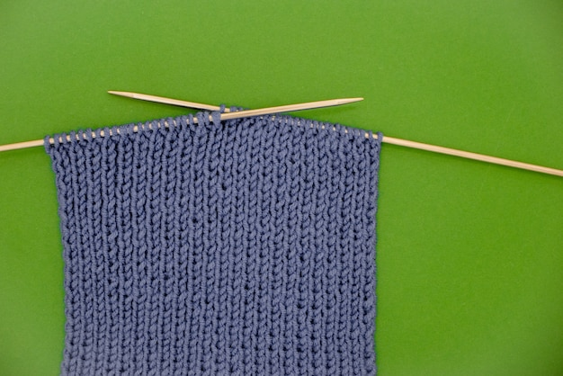 Dark grey knitted  scarf with knitting needles green background.
