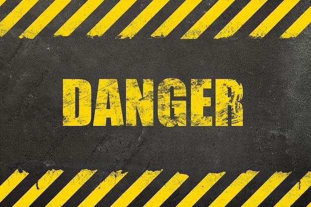 黄色の塗られたグランジ危険サインとストライプとダークグレーのoncrete風化壁の背景