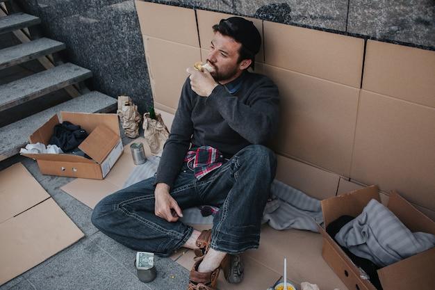 黒髪の汚い男は段ボールに座ってサンドイッチを食べています。彼のポーズはリラックスしています。男は見上げています。彼を取り巻くものはたくさんあります。