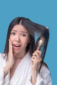 Темноволосая азиатская женщина расчесывает волосы и чувствует стресс