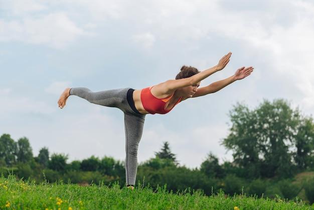 Темноволосая спортивная женщина в удобных серых леггинсах делает позу йоги стоя