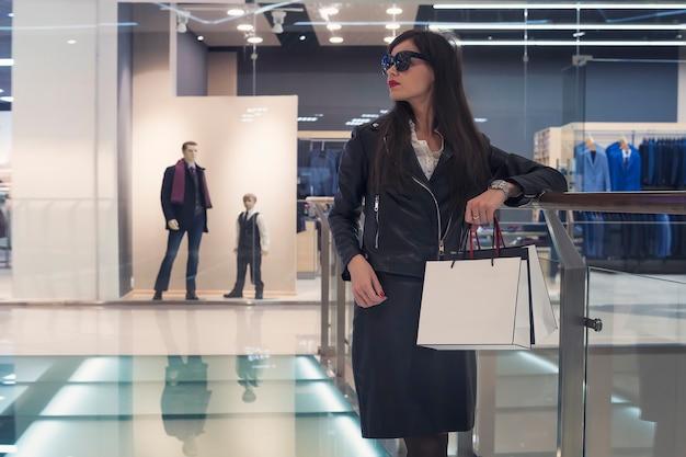 空のショッピングセンターの背景に手すりの近くのガラスの床に一人で立っている黒髪の魅力的な女の子。白いバッグを保持し、モールウォーキングエリアでカメラから目をそらしている眼鏡の女性。
