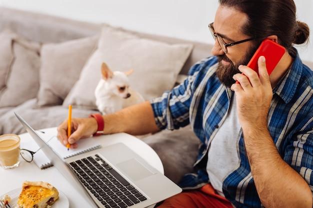 Темноволосый бородатый занятый фрилансер делает заметки, разговаривая с деловым партнером