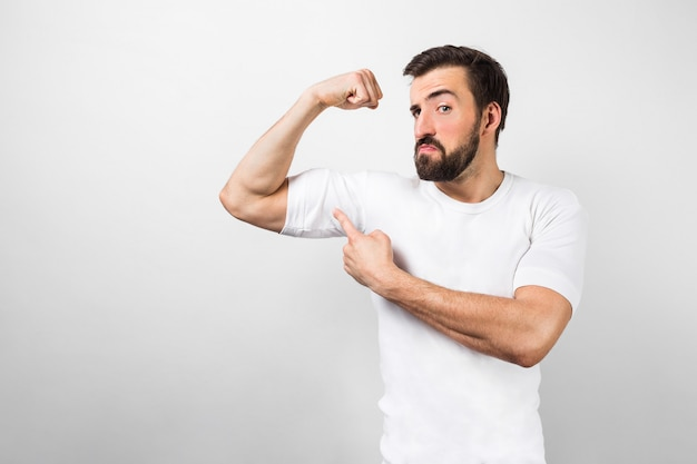 Dark-haired and bearded guy standing near white wall and pointing at his big muscles on his right hand and looking to camera. this guy is confident he has good body shape.