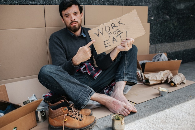 Dark-haired and bearded homeless man is sitting and pointing on piece of cardboard which says work for eat