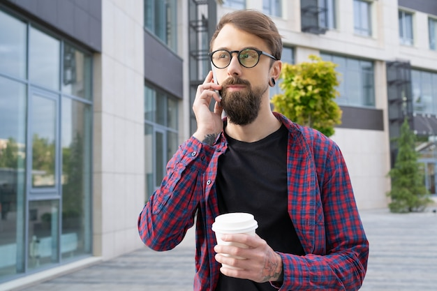 Dark-haired bearded man in eyeglasses talking via smartphone