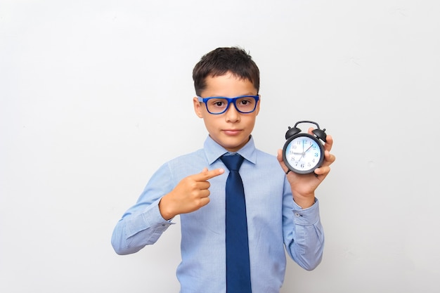 A dark-haired boy in a blue shirt and glasses holds an alarm clock in his hand and points at it with his finger