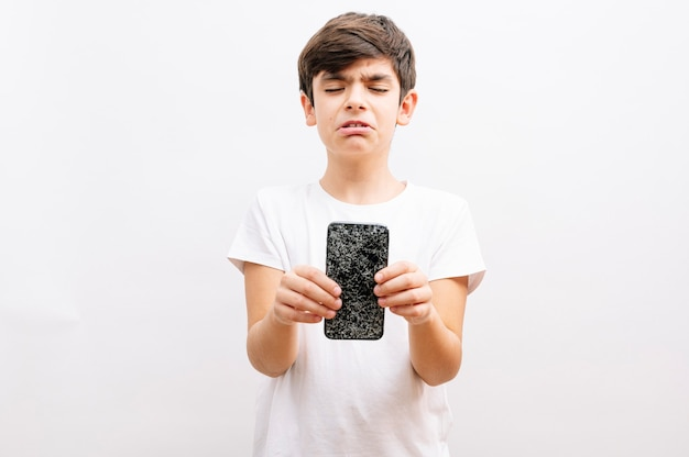 Dark haired boy holding a broken smartphone with a crying expression