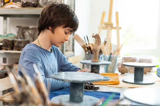 Dark-haired boy sitting and modeling polymer clay figures