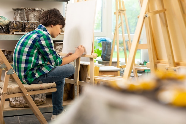 Dark-haired boy sitting near painting easel and drawing