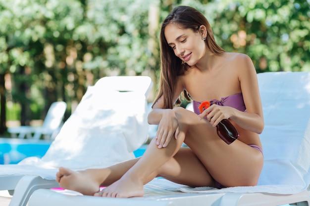 Темноволосая бизнес-леди заботится о своей коже, используя защитный крем перед солнечными ваннами