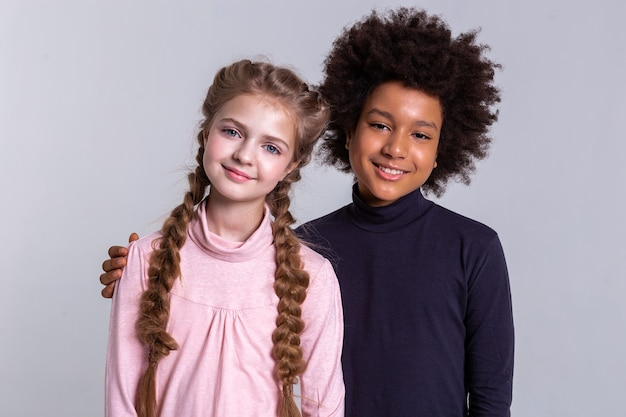 Dark-haired curly boy. smiling african american boy gently hugging his blonde friend while she wearing pink turtleneck