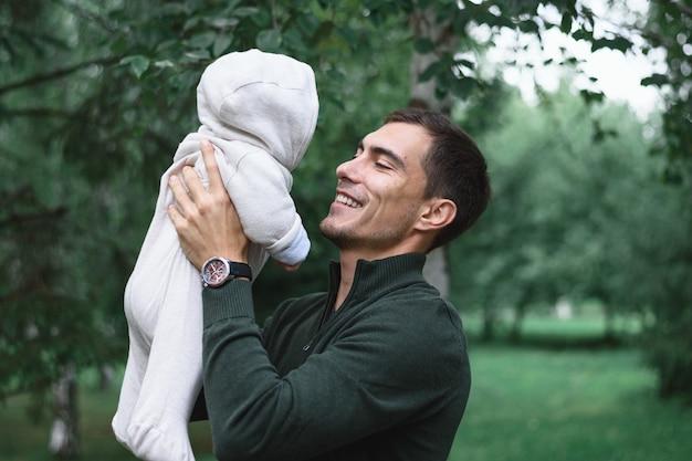 손에 유아 아기와 함께 녹색 재킷에 검은 머리 아빠