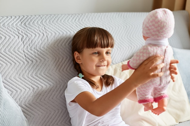 Dark haired female child wearing white t shirt, has pigtails raising her doll, looking at her toy with smile, playing alone while sitting on sofa at home.