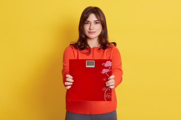 Donna dai capelli scuri che indossa il ponticello casuale arancione che mostra le bilance da pavimento, isolate sopra la parete gialla.