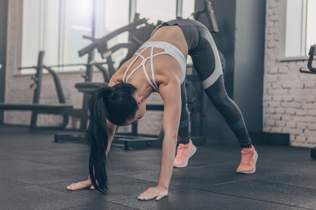 Dark haired fit sportswoman stretching her body before workout at the gym, copy space