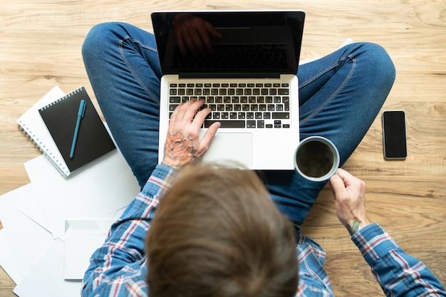 Темноволосый фрилансер печатает на ноутбуке и пьет кофе