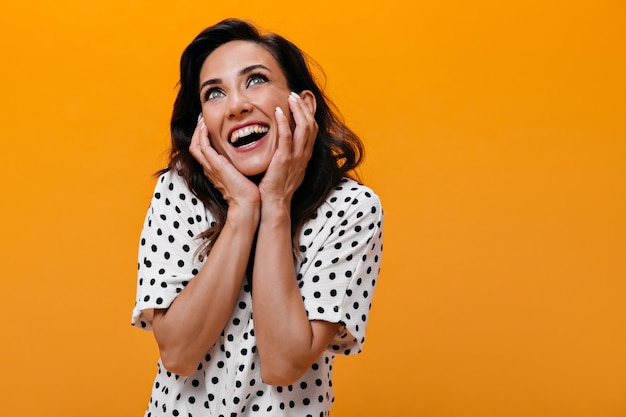 Dark-haired girl dreamily looks up on orange background. surprised woman with green eyes in white polka dot blouse smiling and posing.