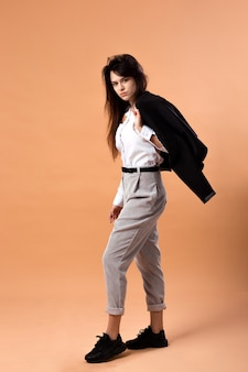 Темноволосая девушка в белой рубашке, серых брюках и черных кроссовках стоит с черной курткой на плече в студии на бежевом фоне.