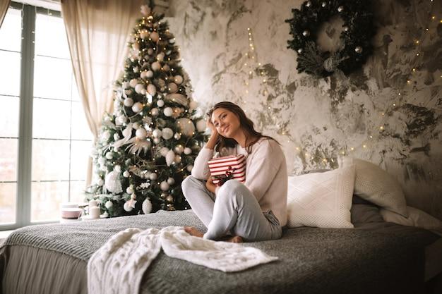 흰색 스웨터와 바지를 입은 검은 머리 소녀는 새해 나무와 촛불로 장식된 방에서 회색 담요와 흰색 베개로 침대에 앉아 손에 새해 선물을 들고 있습니다.
