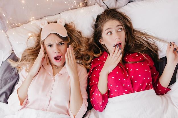 Ragazza dai capelli scuri che esprime emozioni sorprese mentre posa a letto. donna riccia dispiaciuta in eyemask sdraiato sul cuscino.