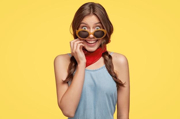 검은 머리 소녀는 즐거운 외모를 가지고 있으며 트렌디 한 음영, 두건 및 진 드레스, 노란색 벽에 모델을 착용하고 남자 친구와 산책 할 준비가되었습니다. 행복한 아가씨는 휴가, 실내 모델을 기뻐합니다.