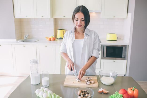 暗い髪の少女は、キッチンと木板にキノコを切るに立っています。