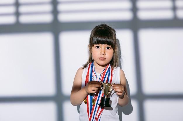 Темноволосая девушка с медалями спортивного чемпионата и трофейным кубком стоит в тени окна с шторами над ней. концепция спорта и победы