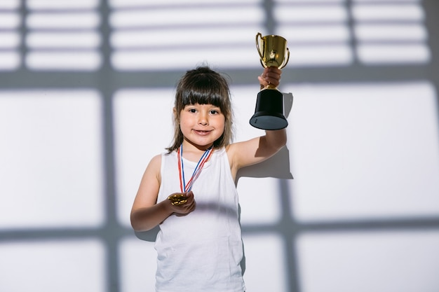 Темноволосая девушка с медалями спортивного чемпионата поднимает руками свой трофейный кубок над тенью окна со ставнями над ней. концепция спорта и победы