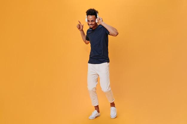 Темноволосый парень в футболке и белых штанах танцует и слушает музыку