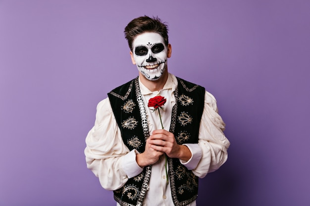 Dark-haired guy with beautiful smile in great mood, posing on isolated wall. photo of mexican with face art and rose in his hands.