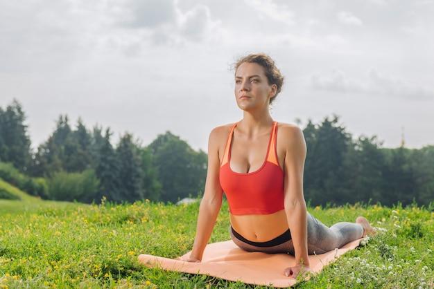 Темноволосая гимнастка укрепляет мышцы при растяжении тела