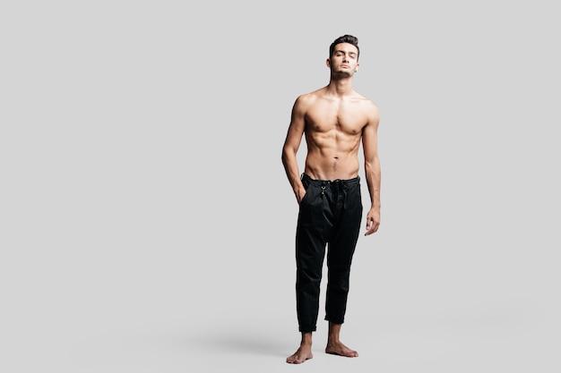 黒のスポーツパンツを身に着けている裸の胴体を持つ黒髪のハンサムな若いダンサーは、白い背景の上の彼のポケットに手を置いて立っています