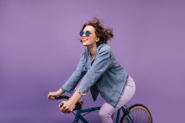 Dark-haired joyful lady chilling on bike. winsome caucasian girl with wavy hair sitting on bicycle.