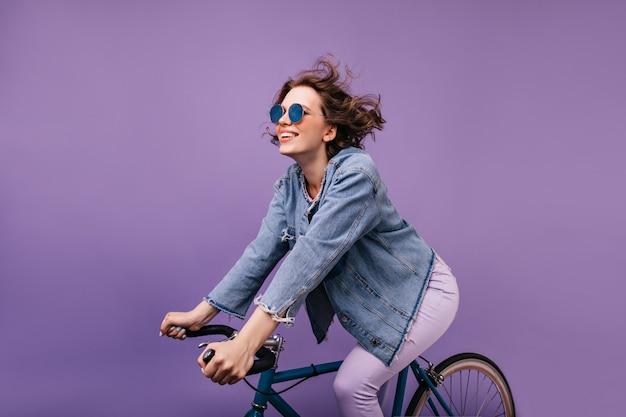 검은 머리 즐거운 아가씨 자전거에 놀아요. 자전거에 앉아 물결 모양의 머리를 가진 winsome 백인 소녀.