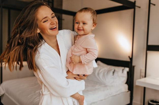 흰 가운을 입은 검은 머리 아가씨와 어린 딸이 밝은 침실에서 놀고있는 동안 진심으로 웃습니다.