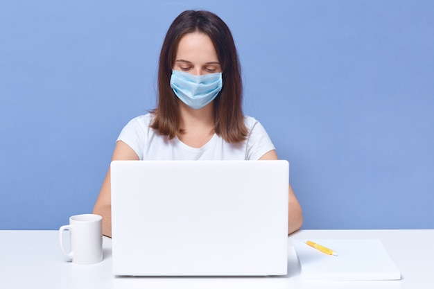 Dark haired lady wearing casual t shirt and medical protective mask working in front of lap top screen, looks concentrated, student female doing online university task, education.