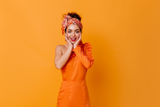 Dark-haired lady with red lipstick dressed in orange dress and aheadband with smile looking at camera on isolated space.