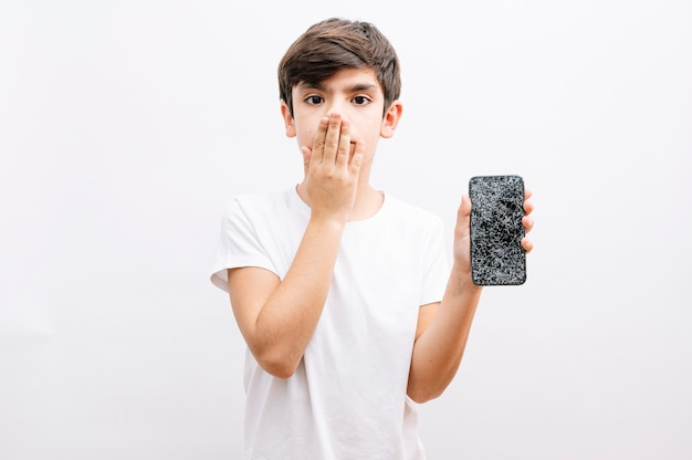 Dark haired little child holding broken smartphone cover mouth with hand shocked with shame for mistake, expression of fear, scared in silence, secret concept