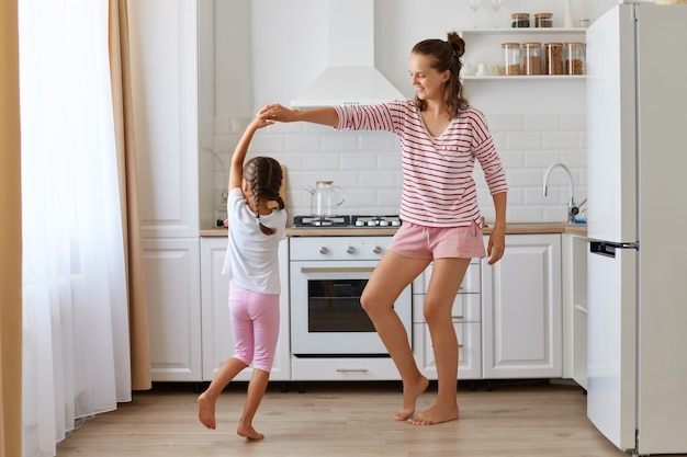 Dark haired little girl dancing with mother, daughter feeling amazing dancing with her loving mother in kitchen, family wearing casual style having fun together.