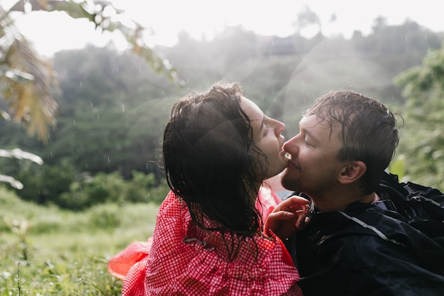 Uomo dai capelli scuri che gode del riposo attivo con la ragazza. outdoor ritratto di coppia di viaggiatori che si rilassano sull'erba.