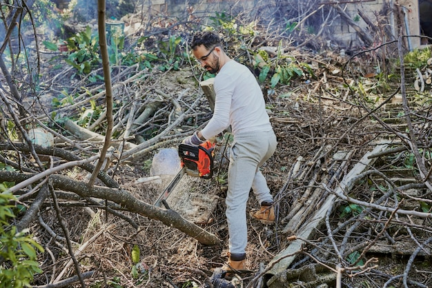 A dark-haired man is clearing the forest using a chainsaw