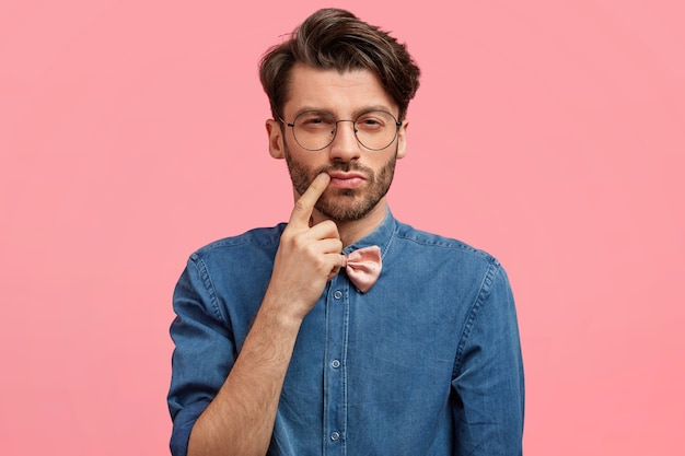 Темноволосый мужчина в розовой бабочке и джинсовой рубашке