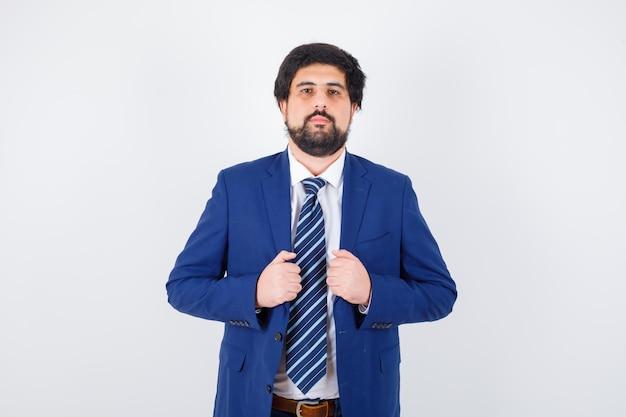 Uomo dai capelli scuri in camicia bianca, giacca blu scuro, cravatta che si aggiusta la giacca, vista frontale.