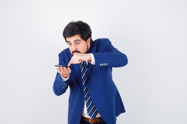 Uomo dai capelli scuri in camicia bianca, giacca blu scuro, cravatta premendo il pulsante del telefono cellulare e guardando a disagio, vista frontale.