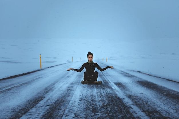 暗い髪のモデルが道路に座ってポーズをとっている
