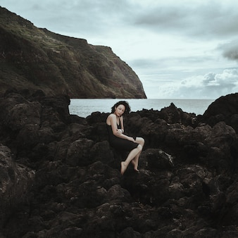 Dark haired model is posing with the mountains and rocks on a background