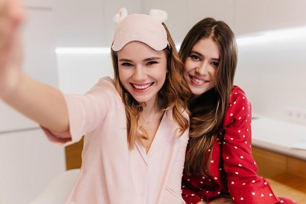 Donna positiva dai capelli scuri in posa mentre la sorella fa selfie. giovani donne sognanti che sorridono la mattina presto.