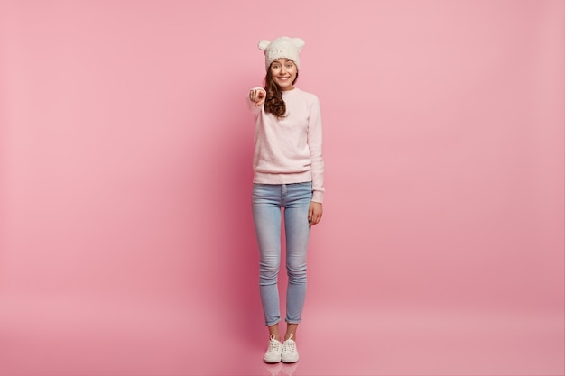 Dark haired positive young european woman wears funny hat with ears, dressed in casual sport clothes